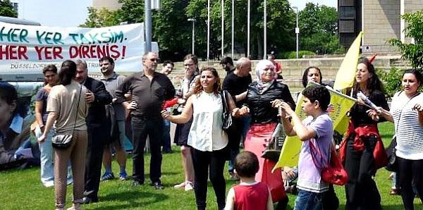Kinder und Erwachsene tanzen vor Protest-Tranparent in türkischer Sprache.