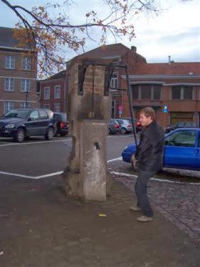 Thomas probeert de pomp op het plein van Hoegaarden. Er komt alleszins geen bier uit, zelfs geen water...