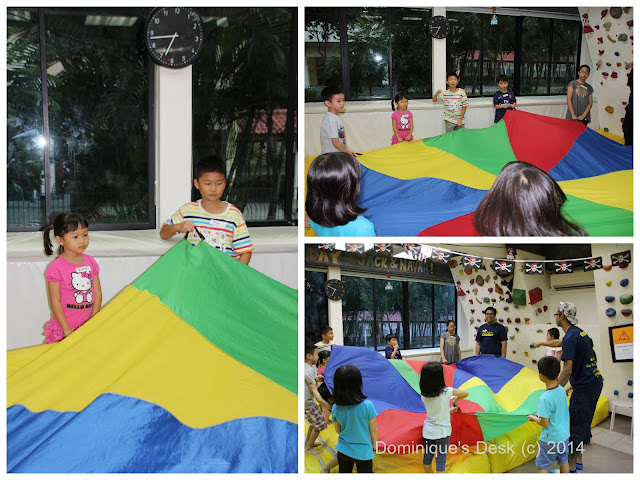The kids playing with the parachute during the lesson.
