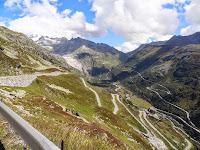 Lacets du Grimselpass au premier plan, montée au Furkapass en fond. Glacier du Rhône sur la gauche.