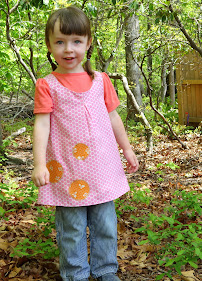 Made with Moxie:Roly-Poly Pinafore pattern review. Girl wearing Roly-Poly Pinafore smiling in the woods.