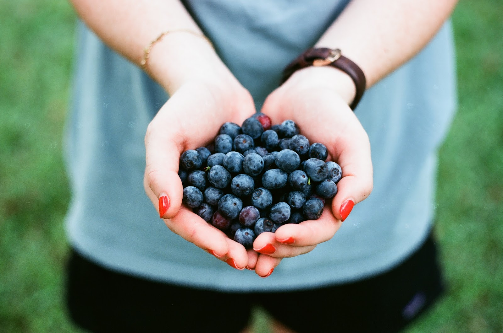 Woman holding blueberries with both of her hands cupped together.