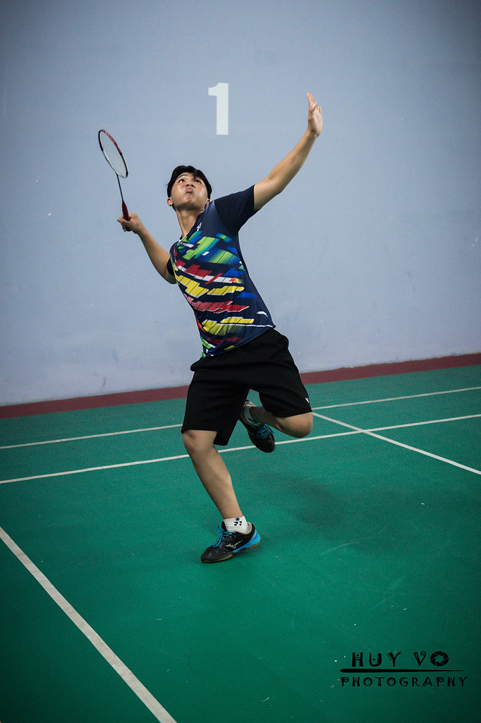 A badminton player has his non racket arm up in front of him, his racket arm behind his head with his elbow bent and a forehand grip.  His eyes are above him on a shuttlecock not in the picture.  He is poised to make a standard forehand smash.