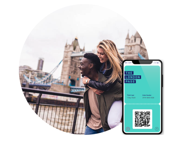 A woman gets carried by her partner as they both smile, walking in front of Tower Bridge in London with an image of the digital London Pass on a mobile phone
