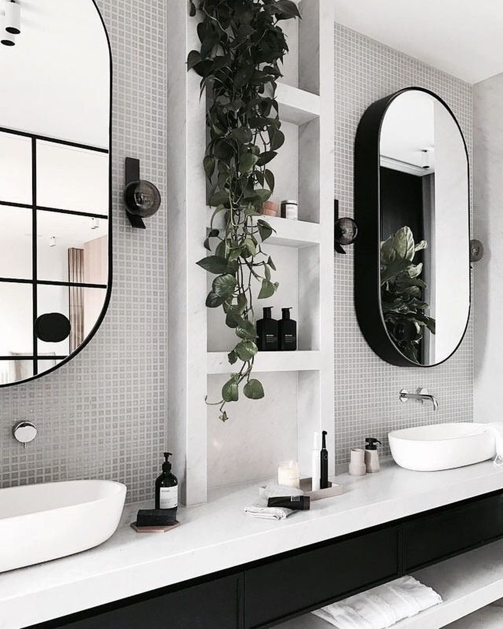 modern black and white bathroom with framed mirrors, tile backsplash, potted plant, white double sinks and black vanity
