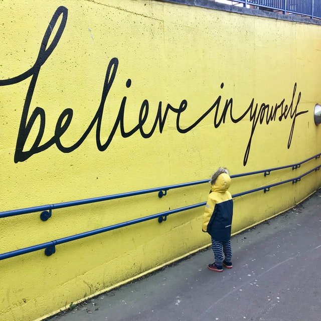 """Little toddler looking at graffiti art that says """"believe in yourself"""""""