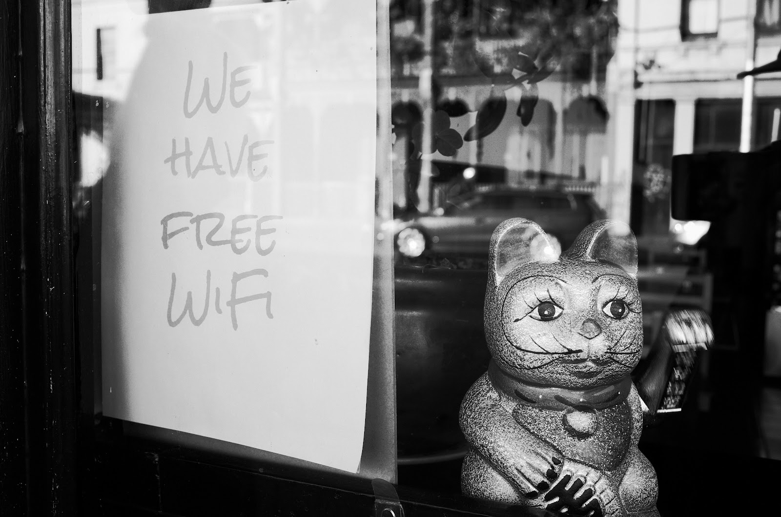 A cat waves in a window next to a Wi-Fi sign