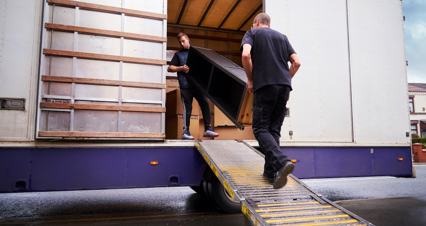 Full-service movers loading furniture onto a moving truck.