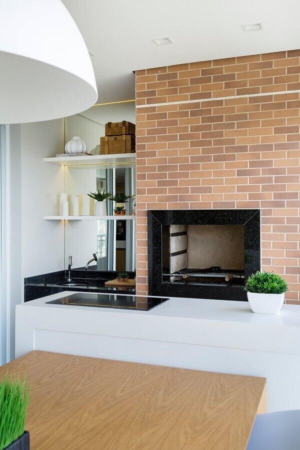 Área gourmet com churrasqueira revestida de tijolinhos e detalhe em granito preto e pia do mesmo material, bancada branca e mesa de madeira.