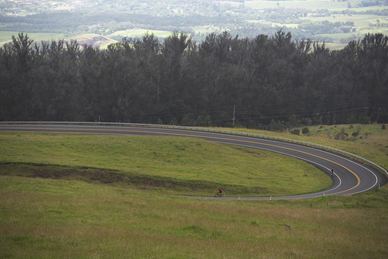 Climbing Haleakala Volcano  by bike - road altitude markers, roadway, clouds and bike