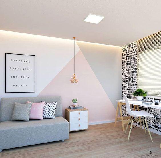 Escritório com parede principal com pintura geométrica em tons claros harmonizando com decoração