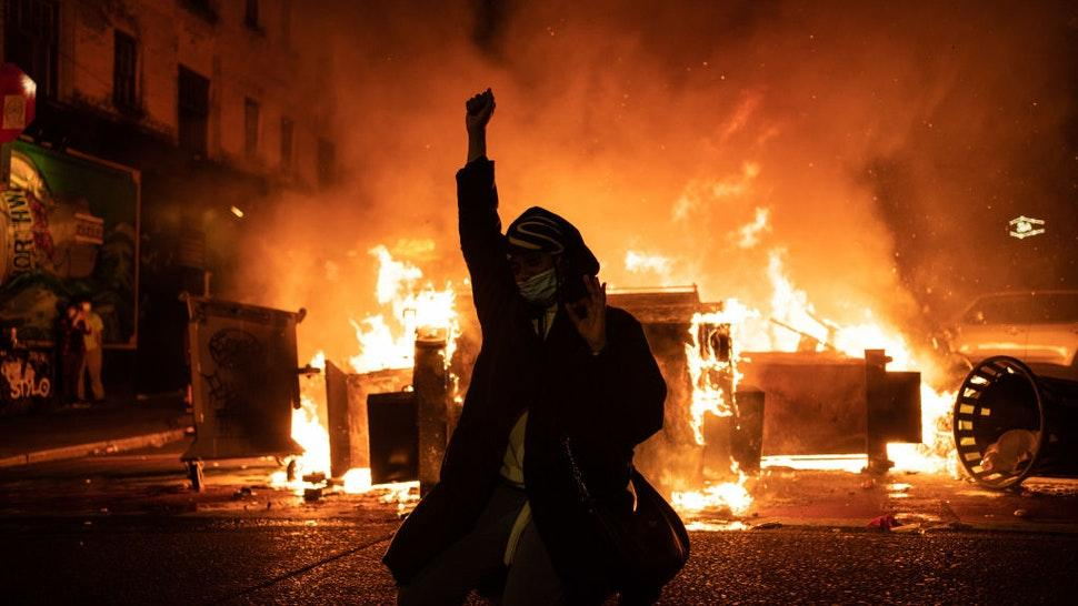 SEATTLE, WA - JUNE 08: A demonstrator raises their fist as a fire burns in the street after clashes with law enforcement near the Seattle Police Departments East Precinct shortly after midnight on June 8, 2020 in Seattle, Washington. Earlier in the evening, a suspect drove into the crowd of protesters and shot one person, which happened after a day of peaceful protests across the city. Later, police and protesters clashed violently during ongoing Black Lives Matter demonstrations following the death of George Floyd. (Photo by David Ryder/Getty Images)