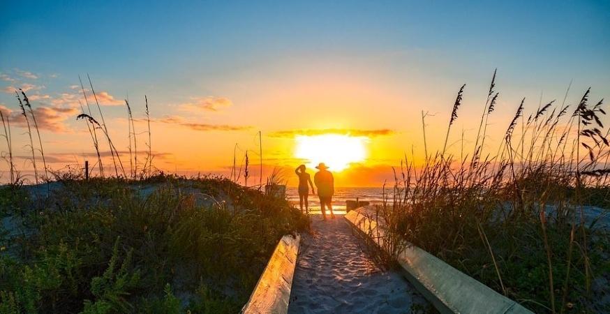 a couple walks on the beach in Jacksonville, FL