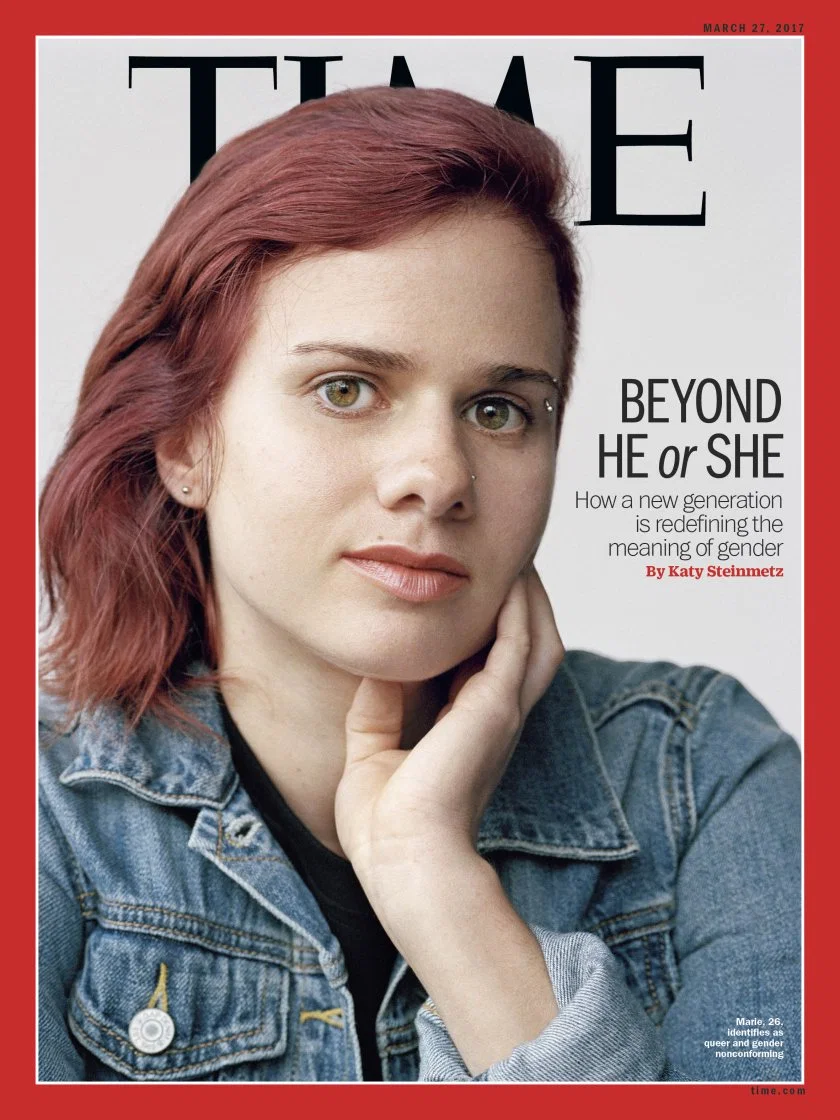 "The cover of Time magazine featuring a queer and gender noncomforming. person named Marie. Marie has red shoulder-length hair, is wearing a denim jacket, and has their hand brought up to their chin. Next to Marie is the superimposed title of the cover story: ""Beyond he or she: How a new generation is redefining the meaning of gender"" by Katy Steinmetz."