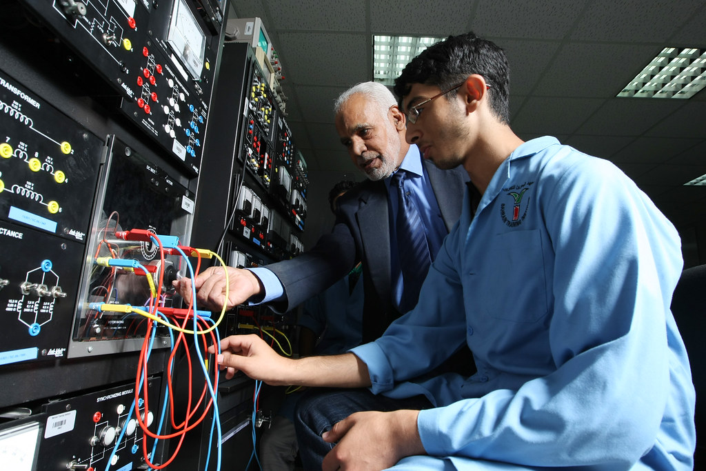 An older gentleman in a suit mentors a young student intern in a lab coat as they explore wiring and connections on a large circuit board.