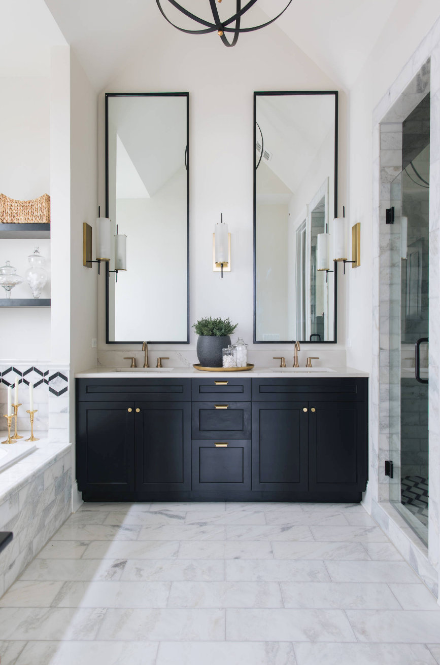 large modern bathroom with black shaker cabinets, large rectangular mirrors, white marble floors and brass hardware