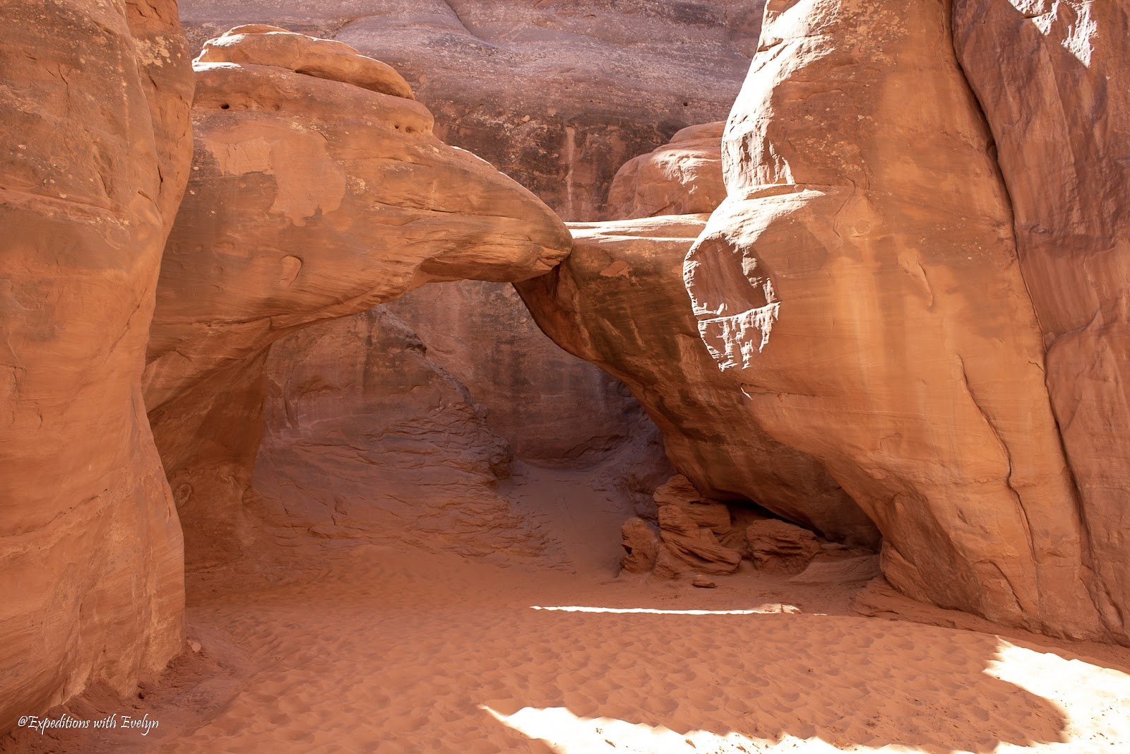 A sandstone arch sits atop a sandy floor in a shaded canyon.