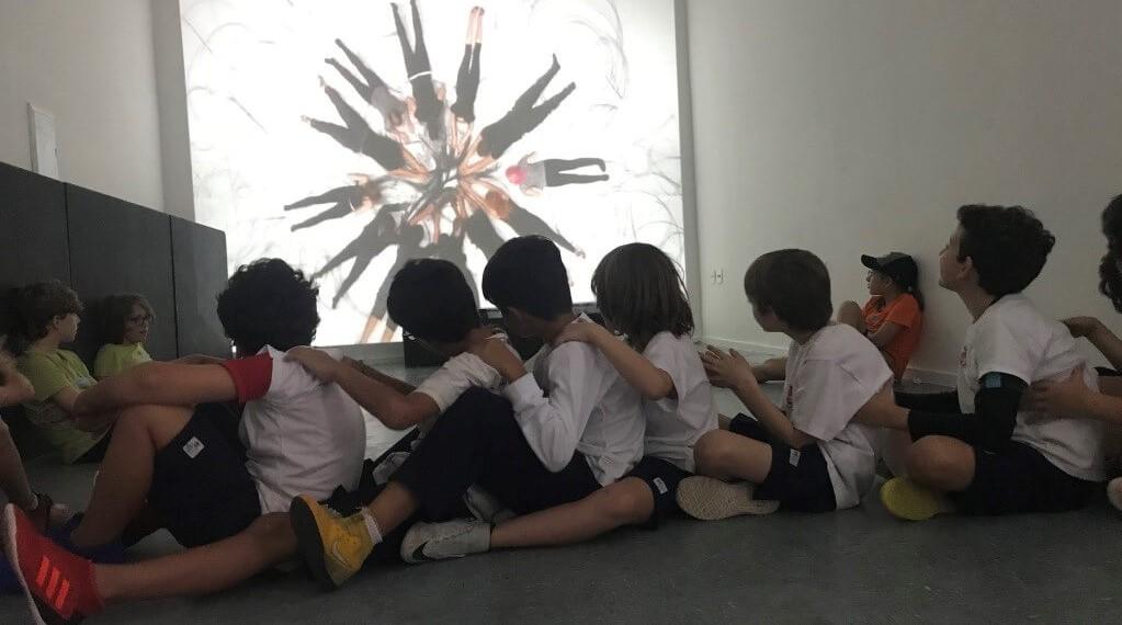 A imagem mostra uma fila de crianças sentadas, umas atrás das outras.