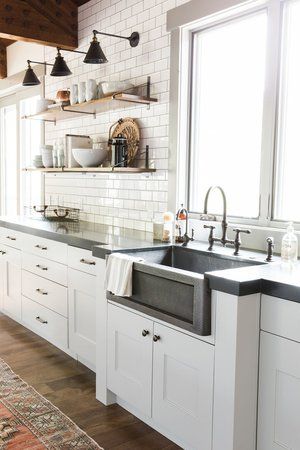 modern white farmhouse kitchen with white subway tile backsplash, cement farmhouse sink, cement countertops, white shaker cabinets, open shelving and wooden beams