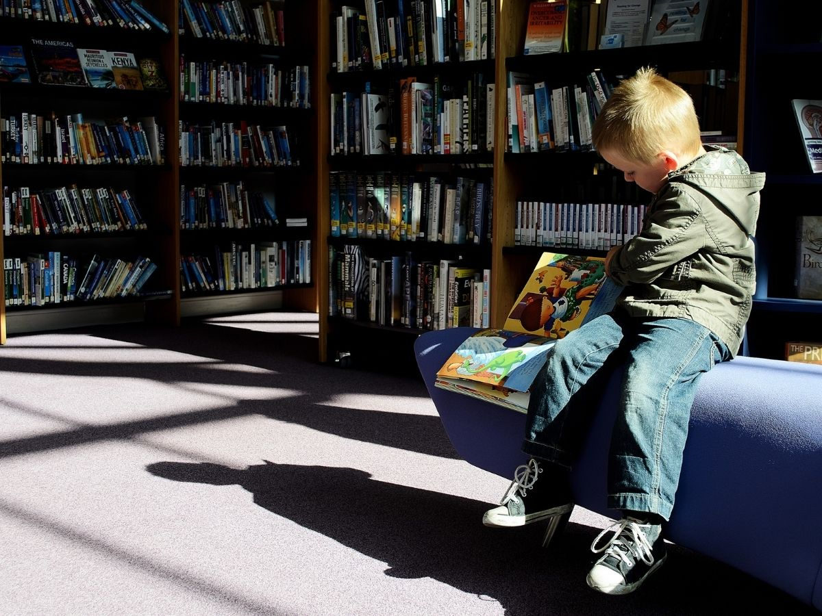 Kid reading a book in the library