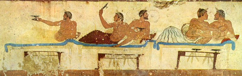 Greek men drinking wine on couches and conversing.