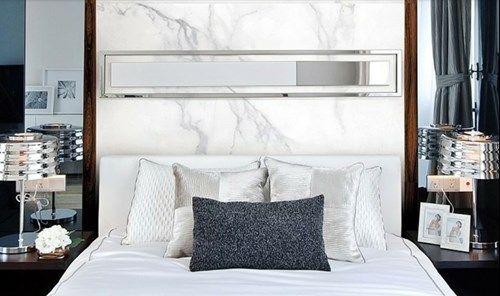 Quarto com cama de casal e parede da cabeceira da cama revestida de porcelanato marmorizado branco.