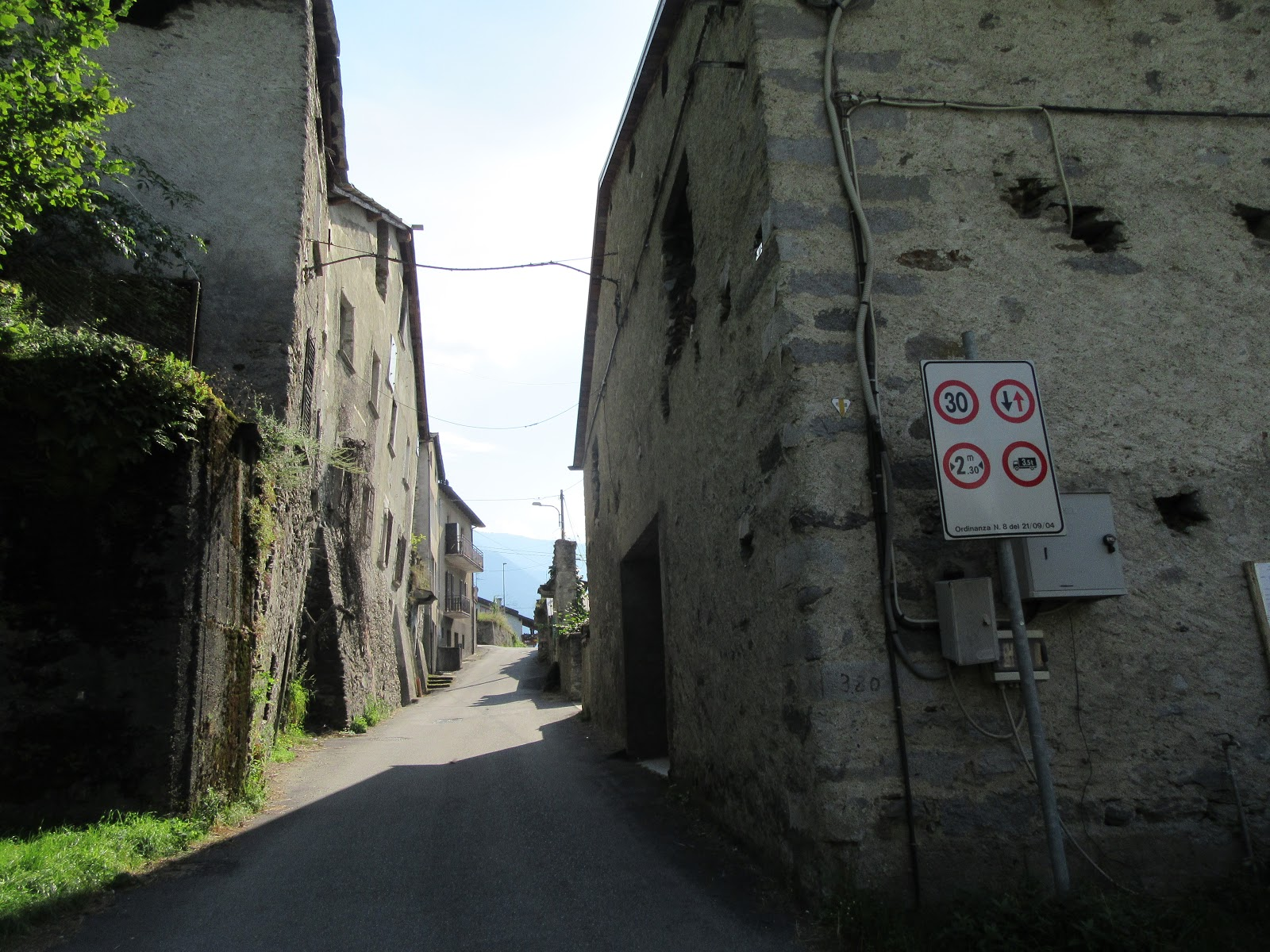 Cycling Passo del Mortirolo from Mazzo di Valtellina - start of climb, narrow road between old buildings