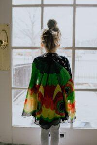 A person facing a door and wearing colorful clothing.