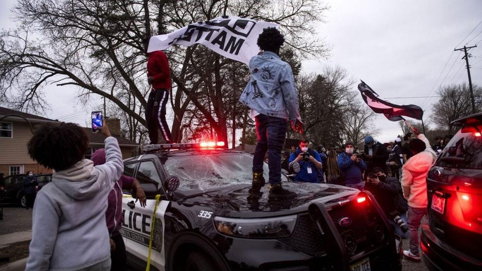 BROOKLYN CENTER, MN - APRIL 11: People stand on a police cruiser as protesters take to the streets after Brooklyn Center police shot and killed Daunte Wright during a traffic stop on April 11, 2021 in Brooklyn Center, Minnesota. A crowd gathered to confront police as they held a line while investigators searched the scene.