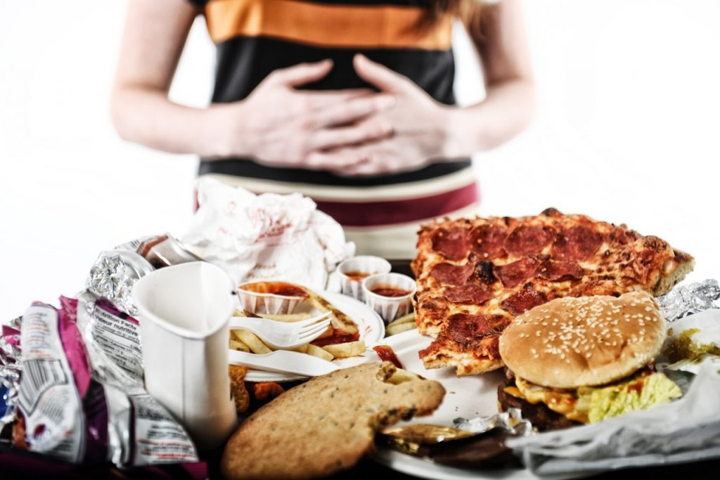 A person holding their stomach with their hands. There is a variety of food on a table, such as pizza and burgers.