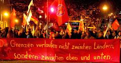 Demonstranten mit Transparent: »Die Grenzen verlaufen nicht zwischen Ländern, sondern zwischen oben und unten.«.