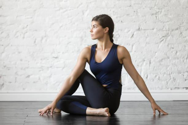 Young attractive woman in Ardha Matsyendrasana pose, studio background Young attractive woman practicing yoga, sitting in Ardha Matsyendrasana exercise, Half lord of the fishes pose, working out, wearing sportswear, black top, pants, indoor full length, studio background stretch and twist stock pictures, royalty-free photos & images