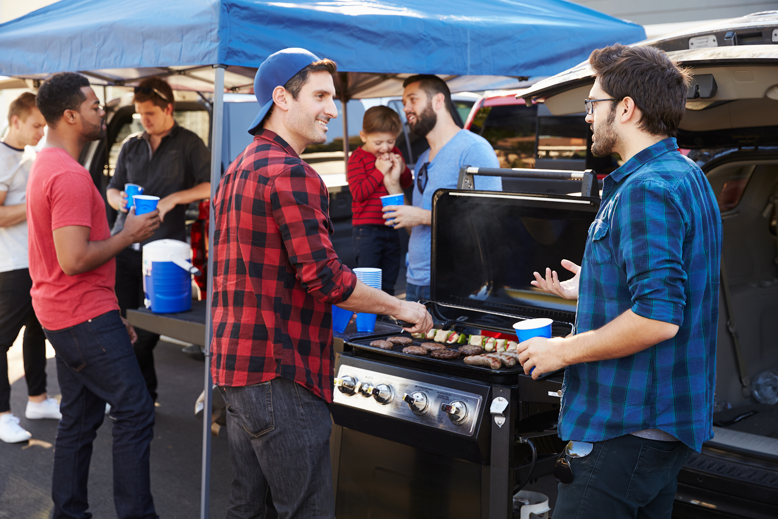 A group of people at an outdoor event with one person grilling on a griddle