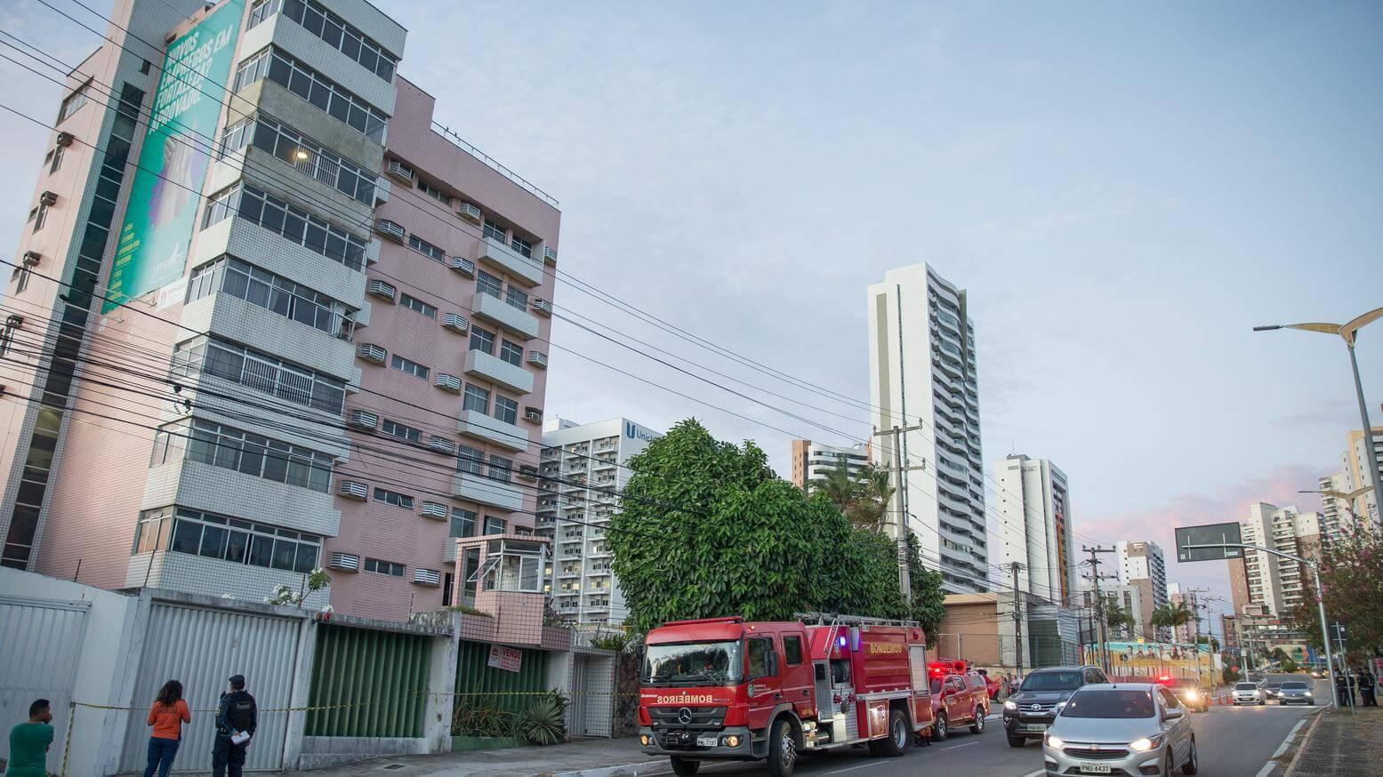 Caminhão de bombeiro parado em frente à um prédio antigo associando à vistoria do corpo de bombeiros em condomínios