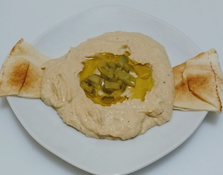 Hummus - Boiled chick peas are mixed with Tahini (sesame paste), lemon juice, olive oil and Dill pickles. Pita chips are shown for decoration, and can be added for $ 1.50 extra. (Vegan, GF)