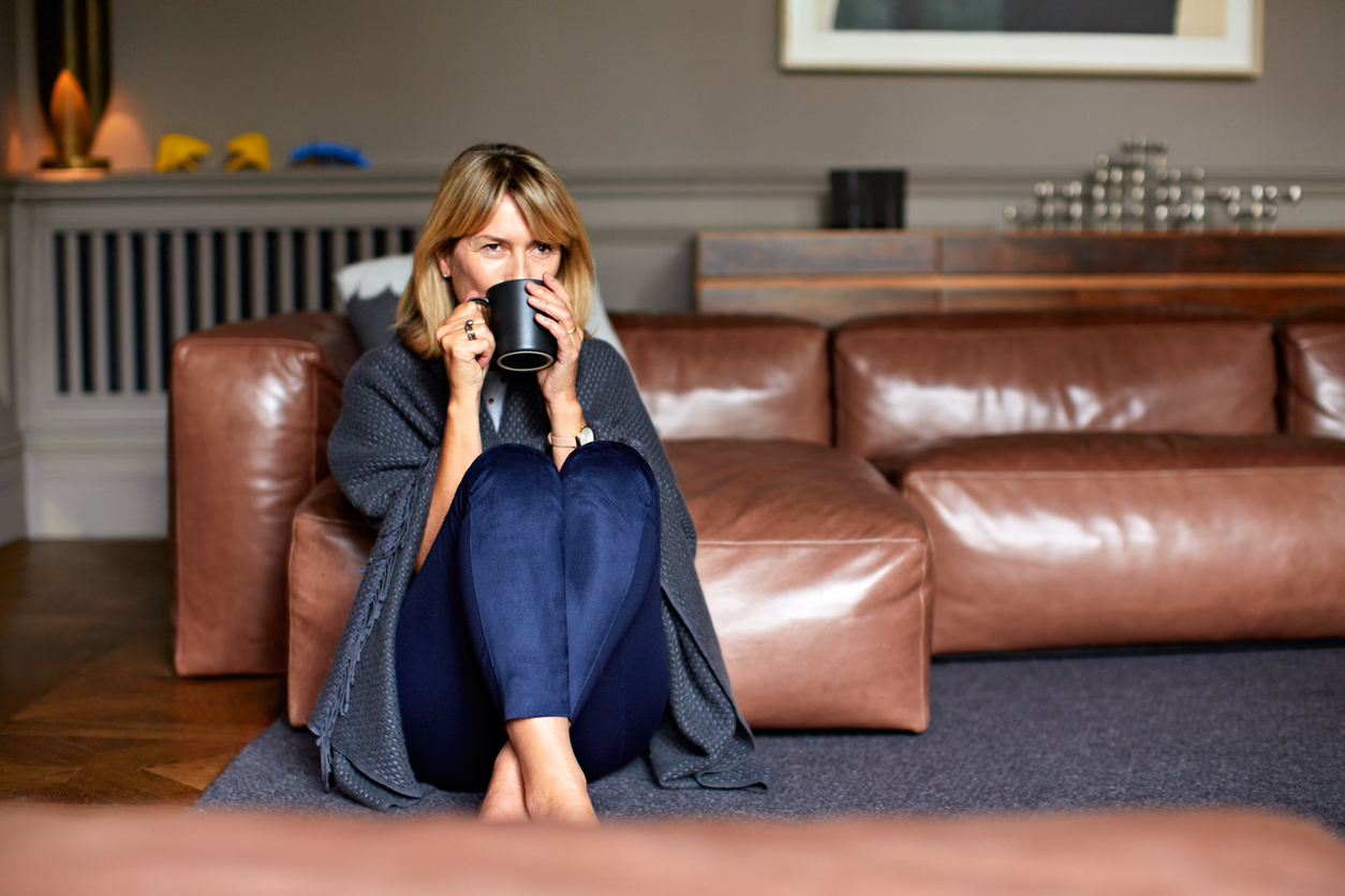 woman sipping out of mug by couch
