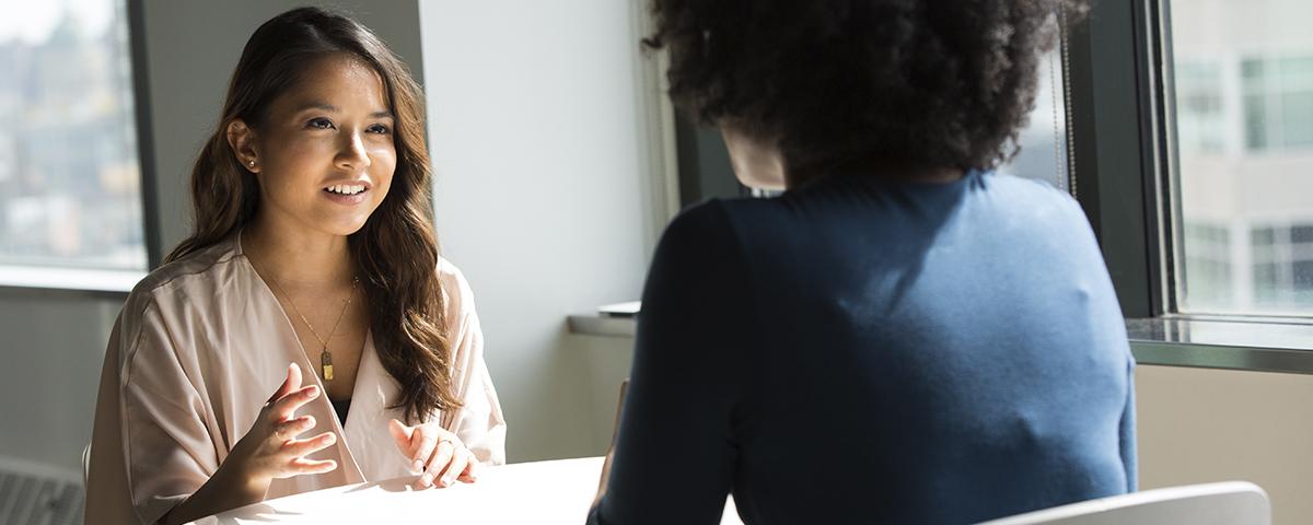 imagem de duas mulheres conversando numa mesa de escritório