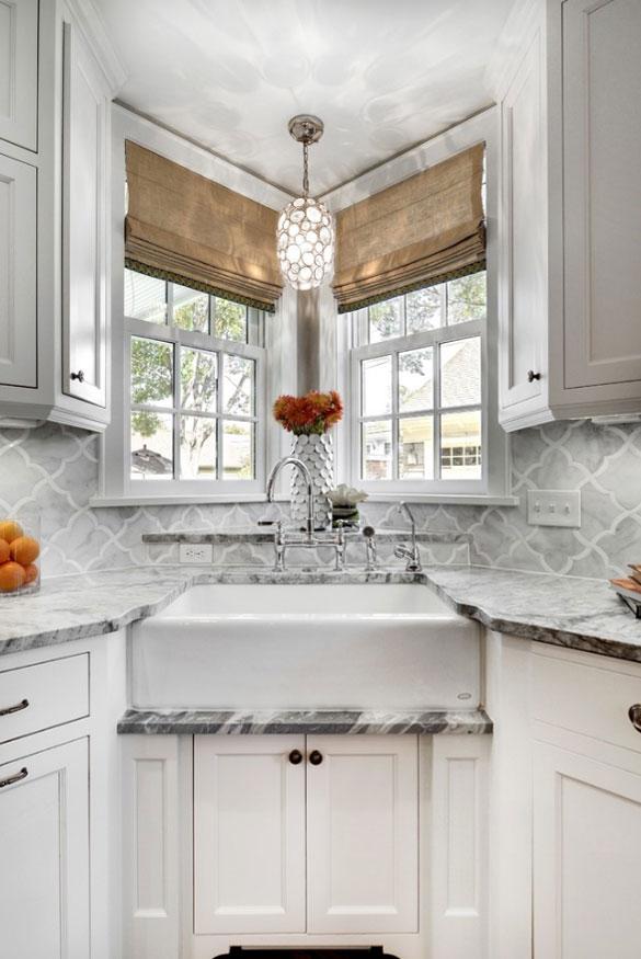 elegant white kitchen with white farmhouse corner sink and white shaker cabinets
