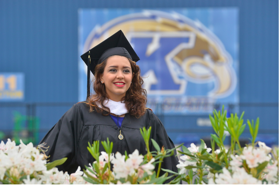 A student smiles after receiving her diploma during a previous commencement ceremony at Dix Stadium.