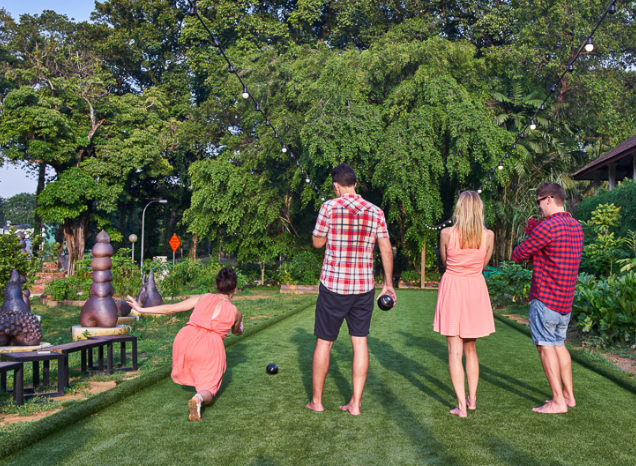 A family playing lawn bowling at Open Farm Community