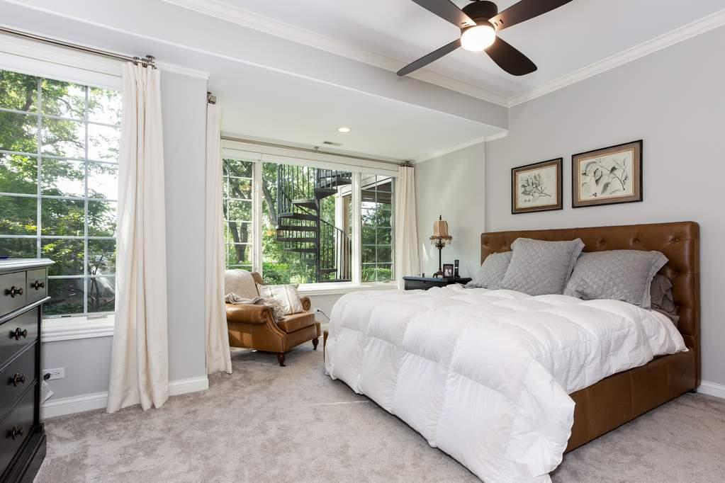Downstairs guest suite with leather headboard and chair, large picture windows and garden views.