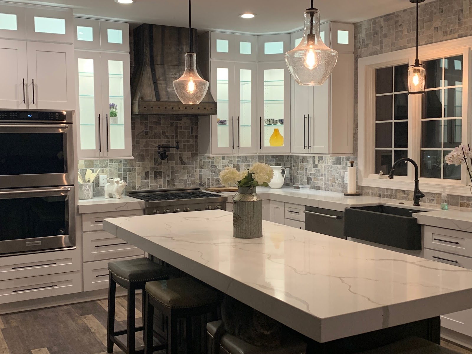 kitchen with white shaker cabinets and thick white quartz countertops. glass pendant lighting hangs above the island, and led cabinet lighting illuminates the interior of the cabinets
