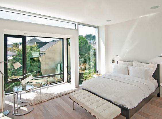Bedroom with a Barcelona bench on the bottom of a bed