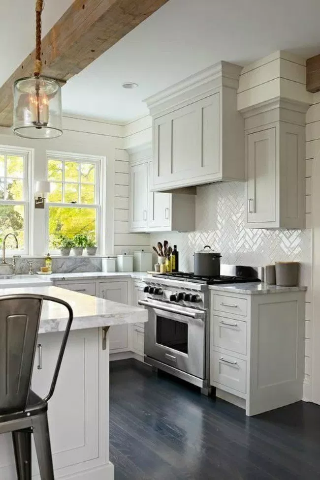 modern farmhouse kitchen with grey shaker cabinets, large island, herringbone backsplash, marble countertops