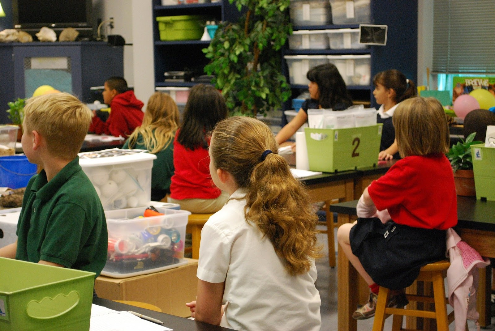 This is a group of students seated at their tables in their elementary classroom. STEM kits are placed throughout the room in matching numbered bins.