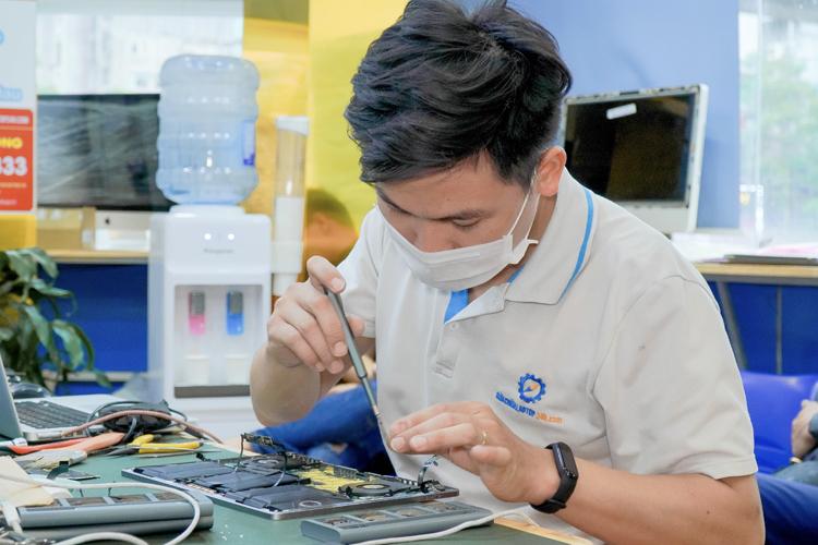 Kỹ thuật viên khắc phục lỗi máy tại trung tâm