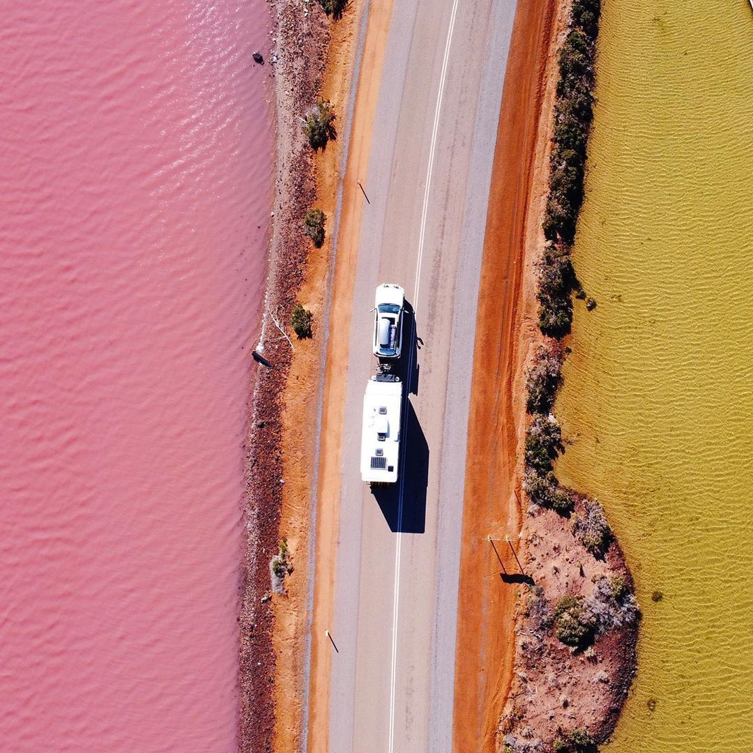 Aerial shot of camper driving on pink lake western australia