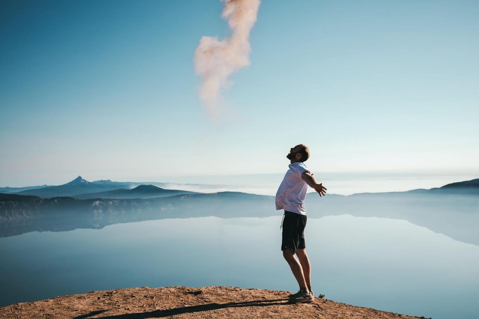 Foto de perfil de um homem com os braços abertos em uma paisagem paradisíaca. Ele aparece sobre um chão rochoso e ergue a cabeça para cima, com a boca aberta. Ele é careca, tem barba cerrada, usa camiseta branca, bermuda escura e tênis com meia. A paisagem é toda em tons de azul, com montanhas que refletem na água, em toda a extensão da imagem.