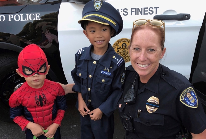 A San Diego police officer visits with two local kids in Halloween costumes