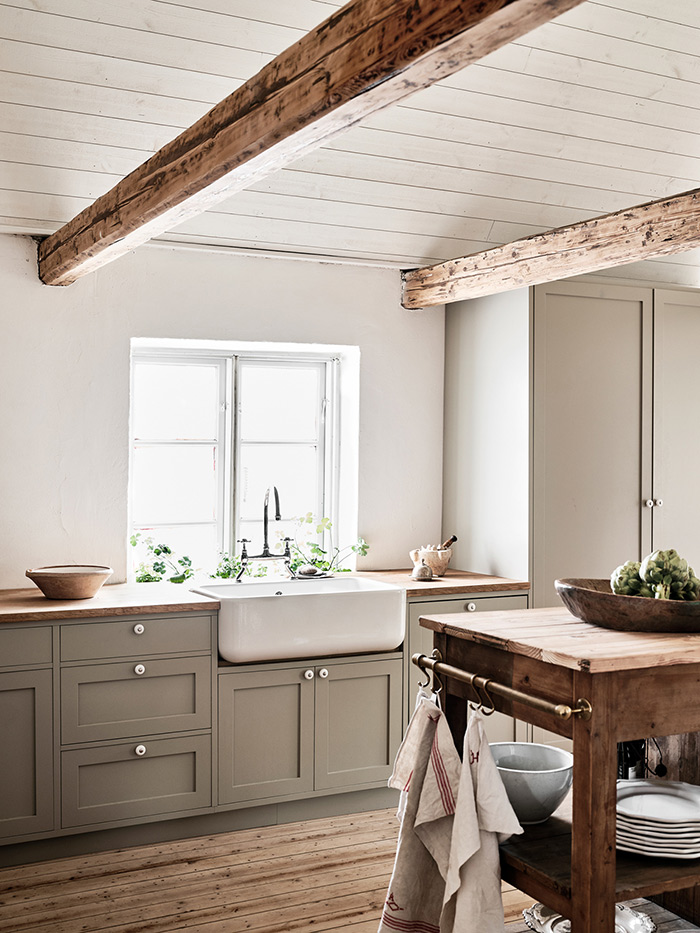 minimalist neutral kitchen with grey shaker cabinets, shiplap ceilings, natural wood beams, farmhouse sink and wood floors